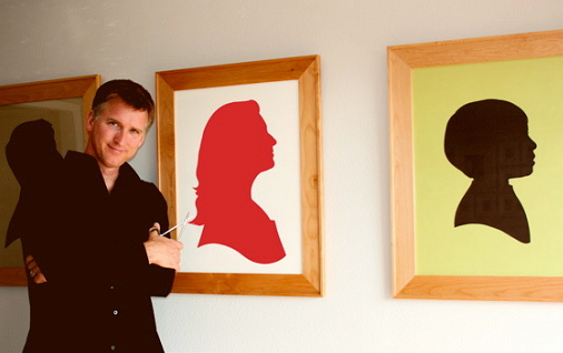 Karl Johnson posing in front of 3 colored silhouette images in frames.