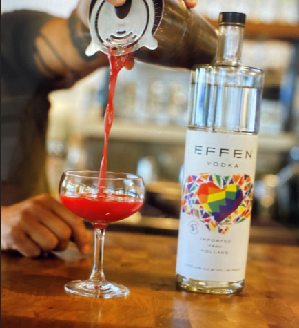 pouring red colored cocktail mix into cup with bottle of Effen Vodka.