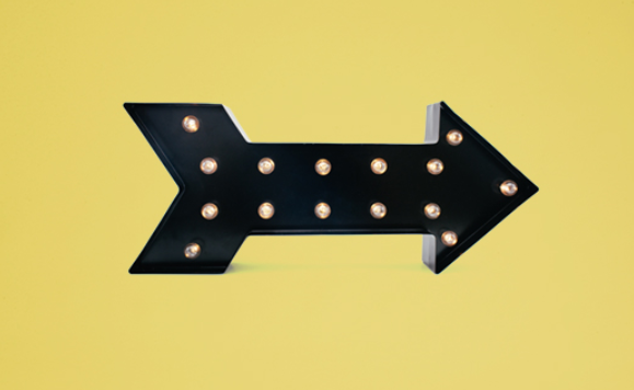yellow background with image of decorative black arrow decorative with light bulbs.