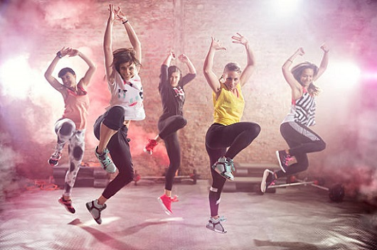 5 women jumping in the air in middle of zumba choreography.