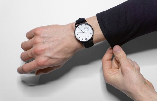 male hand wearing All Mies watch, white face with black band, wearing black long sleeve.