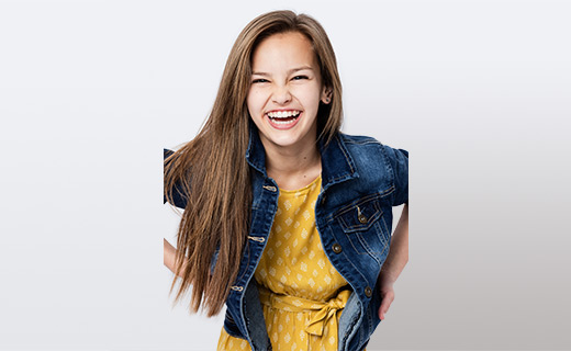 Young girl in a yellow dress and jean jacket smiling
