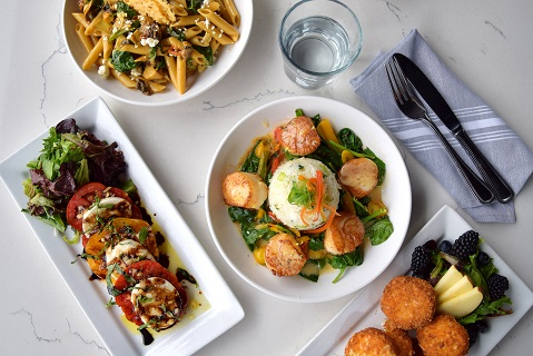 Scallop dish with salmon, tomato & cheese, and pasta dishes on table with utensils.