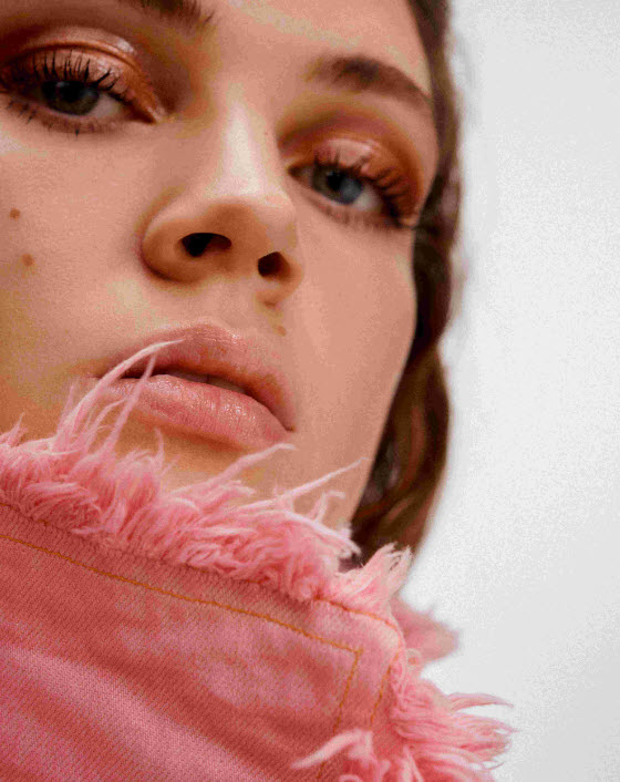 close up of brunette woman's face with makeup on and pink collared coat with fur trim