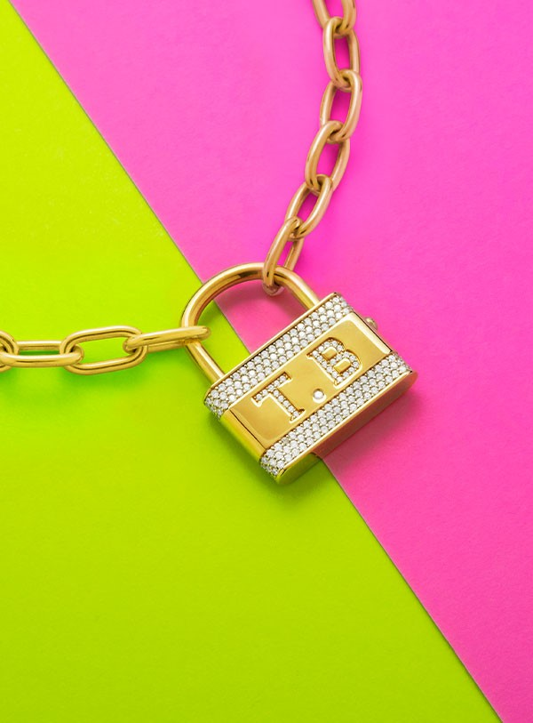 Green and pink background with gold chain and gold and silver locket with initials T.B.