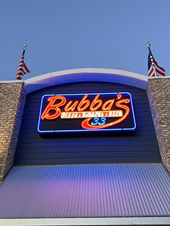 Bubba's 33 exterior shot of the neon red sign flanked on either side by two American flags