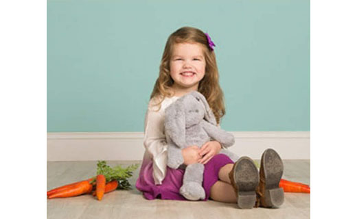 Girl holding gray bunny with carrots around her.