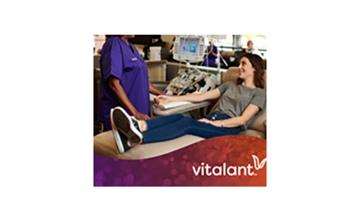 Vitalant representative and girl sitting in chair donating blood. Vitalant logo is included in the image.
