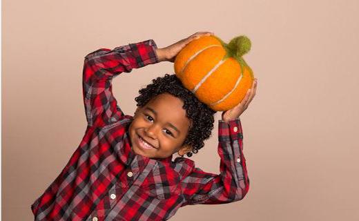 Boy in plaid shirt leaning sideways with a pumpkin prop on his head.