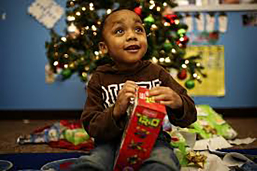 Boy sitting in front of a Christmas tree opening a gift.