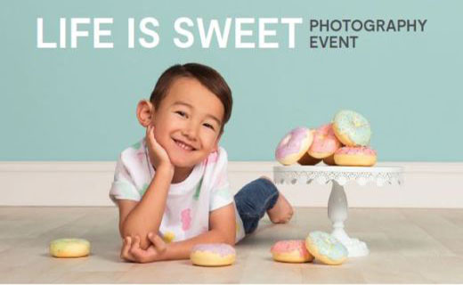 Boy smiling and laying on gray floor with donuts. Teal background with the words Life is Sweet Photography Event.
