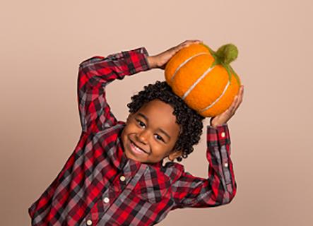 Boy wearing plaid shirt holding pumpkin on his head.