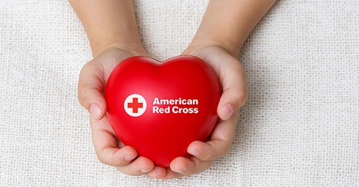 pair of hands holding red heart with the words American Red Cross on it