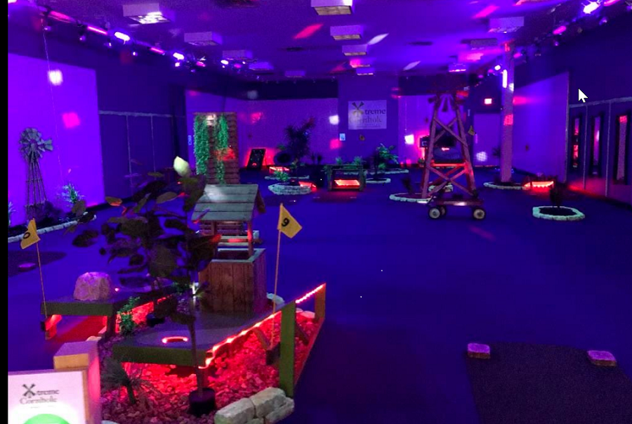 Picture of cornhole areas that have artificial plants, cornhole boards in neon green and a red wagon set up on blue carpet under blacklights.