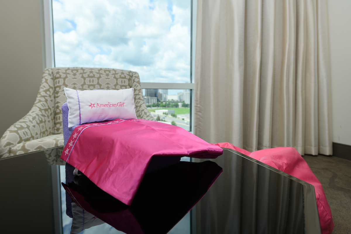 Miniature American Girl bed with white pillow and pink blanket placed on top of a black table with a window and a couch in the background.