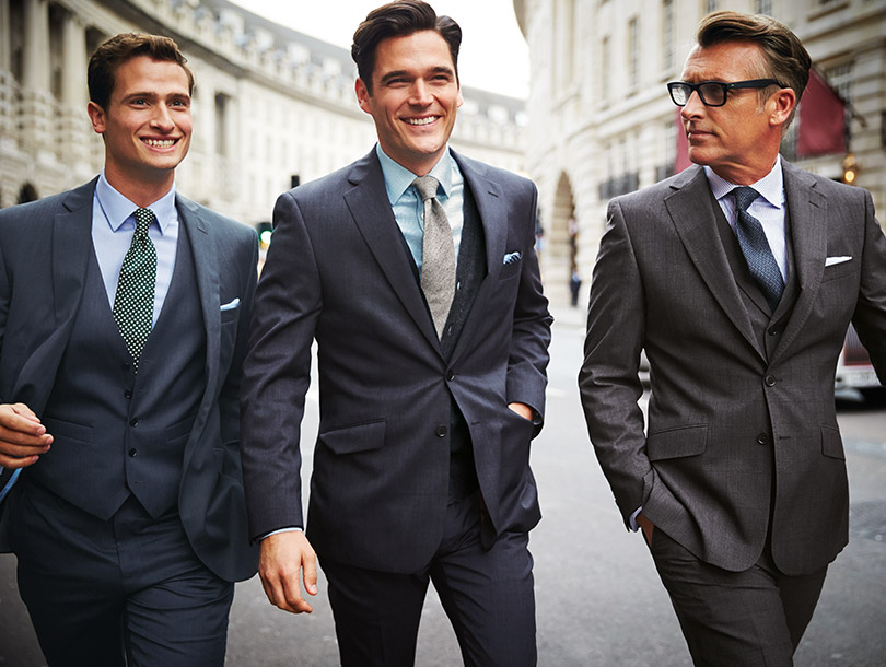 Three men wearing suits while walking down a street.