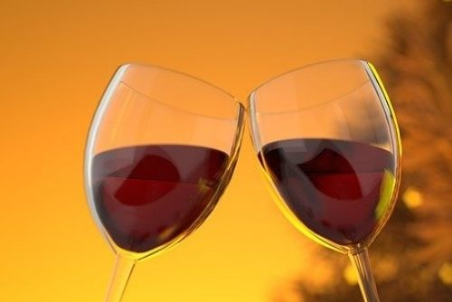 Two wine glasses filled with red wine clinking together.