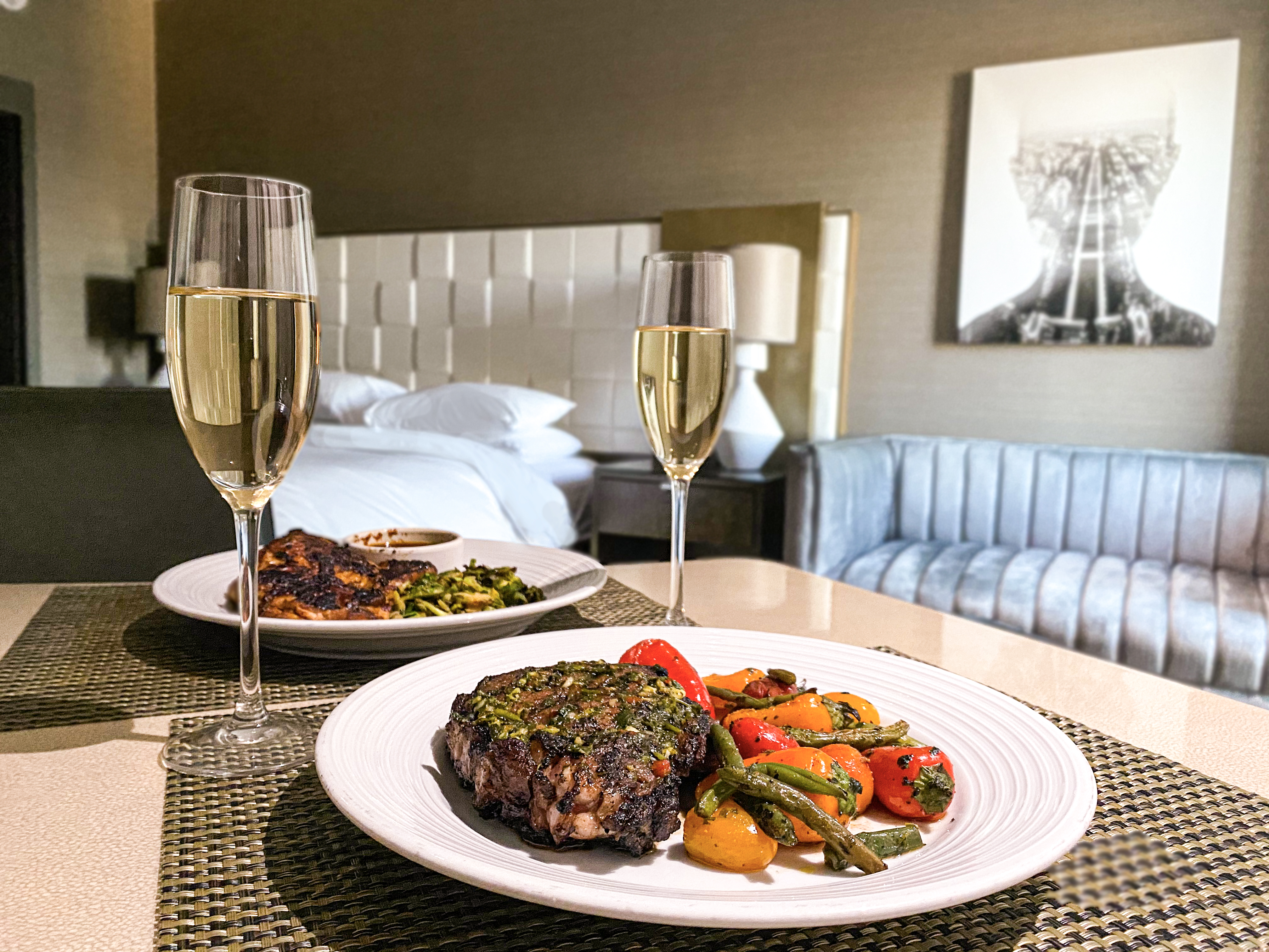 Table with champagne glasses filled up and two plates with vegetables and meat. All inside a hotel room.