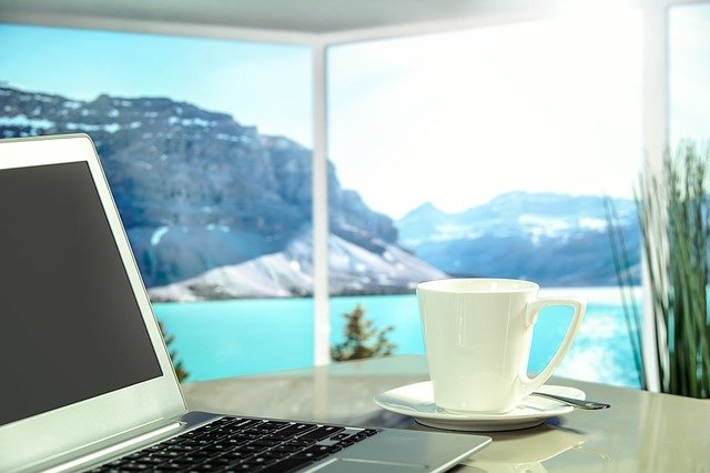 White coffee cup on a plate next to a laptop with a beautiful mountain and lake in the background out the window.