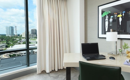 Hotel room with window open onto pretty suburban landscape with laptop on the desk