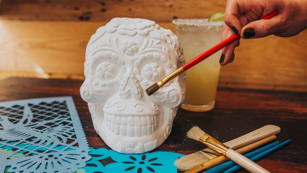 White decorated skull on a table being painted by a red paint brush next to a yellow drink.