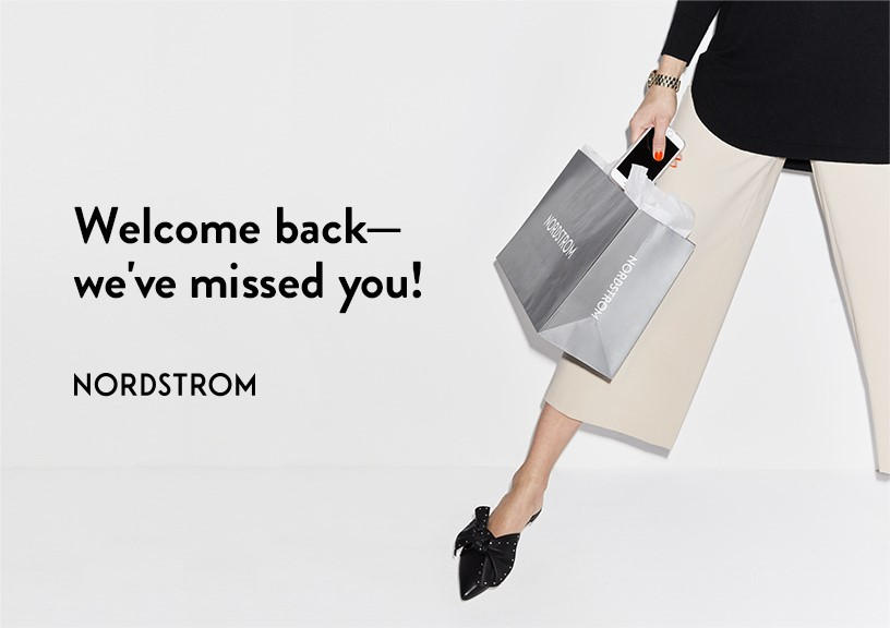 Welcome back message with individual holding Nordstrom bag and cell phone.