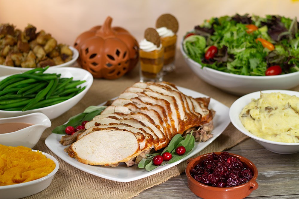 A plate of stuffing, a plate of green beans, a plate of sliced turkey, a bowl of cranberries, a bowl of mashed potatoes, a bowl of salad, a bowl of squash, and a pitcher with gravy all on a wooden table.