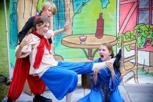 A boy and a girl holding up another girl during a scene for the Traveling Players play.