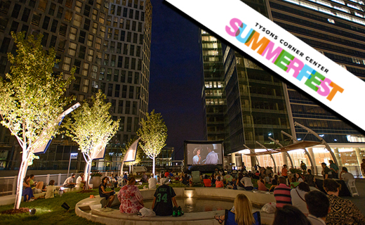 A crowd sitting on Tysons Corner Center Plaza while watching a movie.