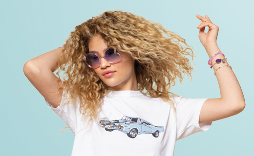 Girl with curly hair and sunglasses dancing.