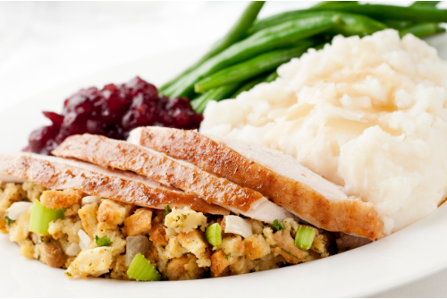 Stuffing, turkey, mashed potatoes, green beans, and berries on a plate.