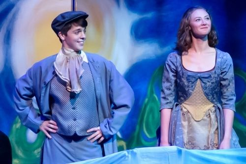Boy and girl smiling on a stage during a play.