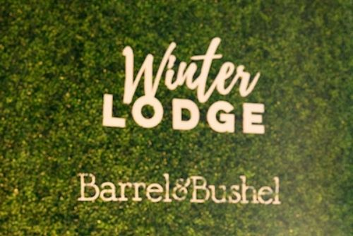 Barrel & Bushel Winter Lodge written in white with a green background.