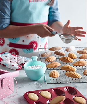 Image of young girl in an American Girl apron making madeleine cookies.