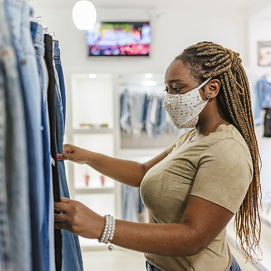 Lady wearing face covering, holding jeans
