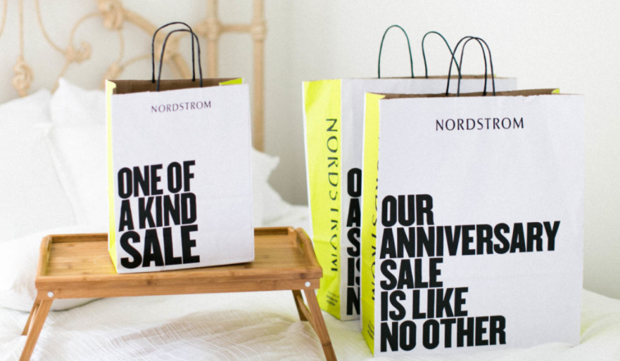 Nordstrom shopping bags on a bed