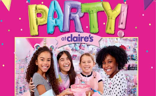 Four girls at a birthday party wearing fun clothes, smiling, and gathered around a plate of cupcakes. 