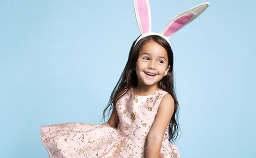 Little girl with pink dress and easter bunny ear headpiece.