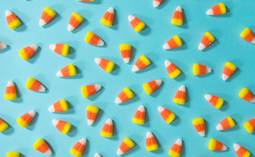 Multiple pieces of candy corn placed on a blue green background