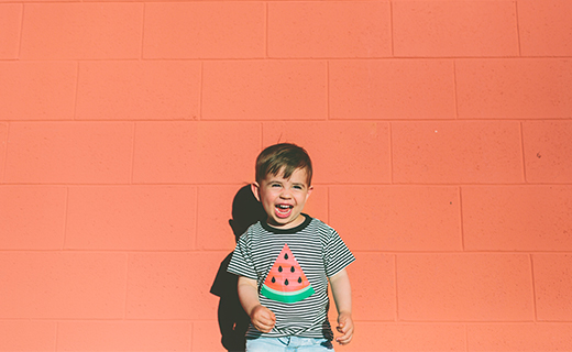 image of little boy standing against an orange wall laughing.
