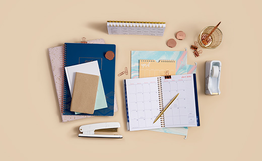 Journals, calendars and office supplies on a beige background.