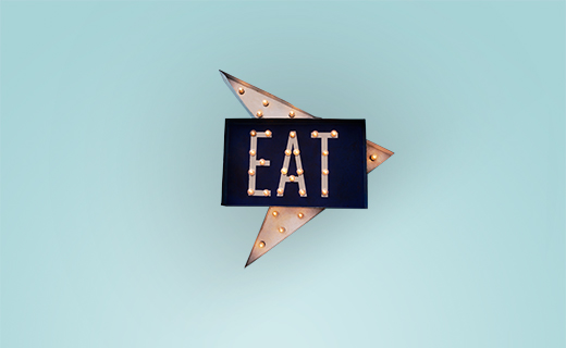 Lit up sign with EAT displayed. Blue background.