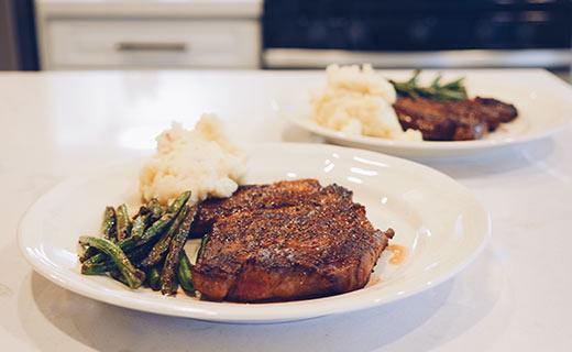 plate with steak, green beans and mashed potatoes