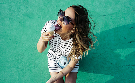 girl wearing a stripped dress wearing shades with a camera & holding an ice cream smiling