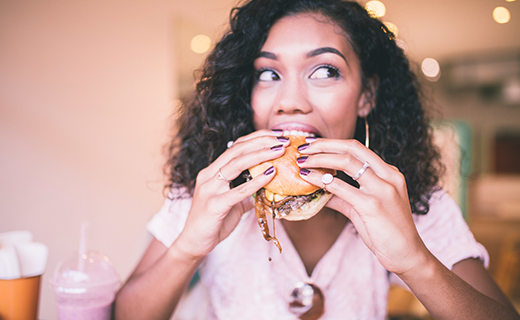 Woman in pink blouse biting into a burger