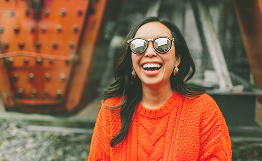 girl laughing wearing shades in an orange fall sweater top.