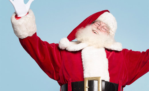 Santa in his red suit with his arms spread open wide, laughing.
