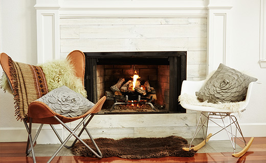 Two chairs by a white fireplace.