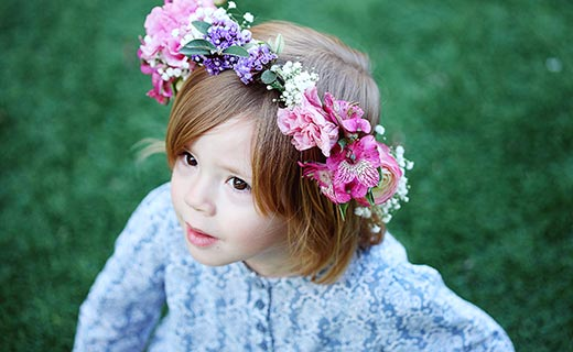 little girl wearing a flower crown and looking up