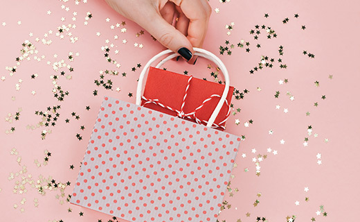 hand holding a small polka dotted gift bag against a glitter star backdrop.